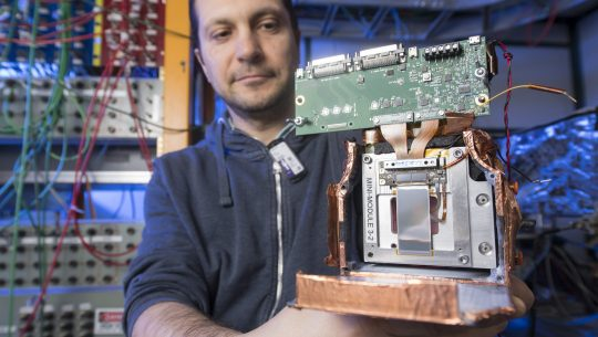 Fermilab engineer Lorenzo Uplegger holds a prototype of the final CMS tracking modules for testing. Photo: Reidar Hahn