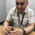 (1/2) Abri Credit Union's Amy Scroggins has kept a Rubik's Cube at her desk since early this year. Jesus Orduna, pictured here, recently spied it and asked if he could try to solve it. Photo: Amy Scroggins, people