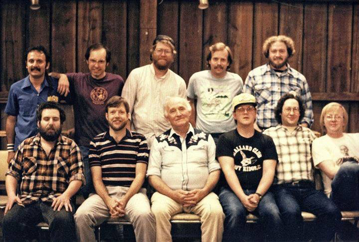 "Chicago Barn Dance Company musicians in 1989 with special guest Lotus Dickey (front row, third from left), and others. Juel Ulven (front row, far right) is the president of the Fox Valley Folklore Society and also runs sound at the dances. Back row, from left: Tony Scarimbolo, Paul Watkins, Fred Campeau, Jim Nelson, Phil Cooper. Front row, from left: Marc Gunther, Paul Tyler, Lotus Dickey, Lynn ""Chirps"" Smith, John Terr, Juel Ulven. Photo courtesy of Juel Ulven"