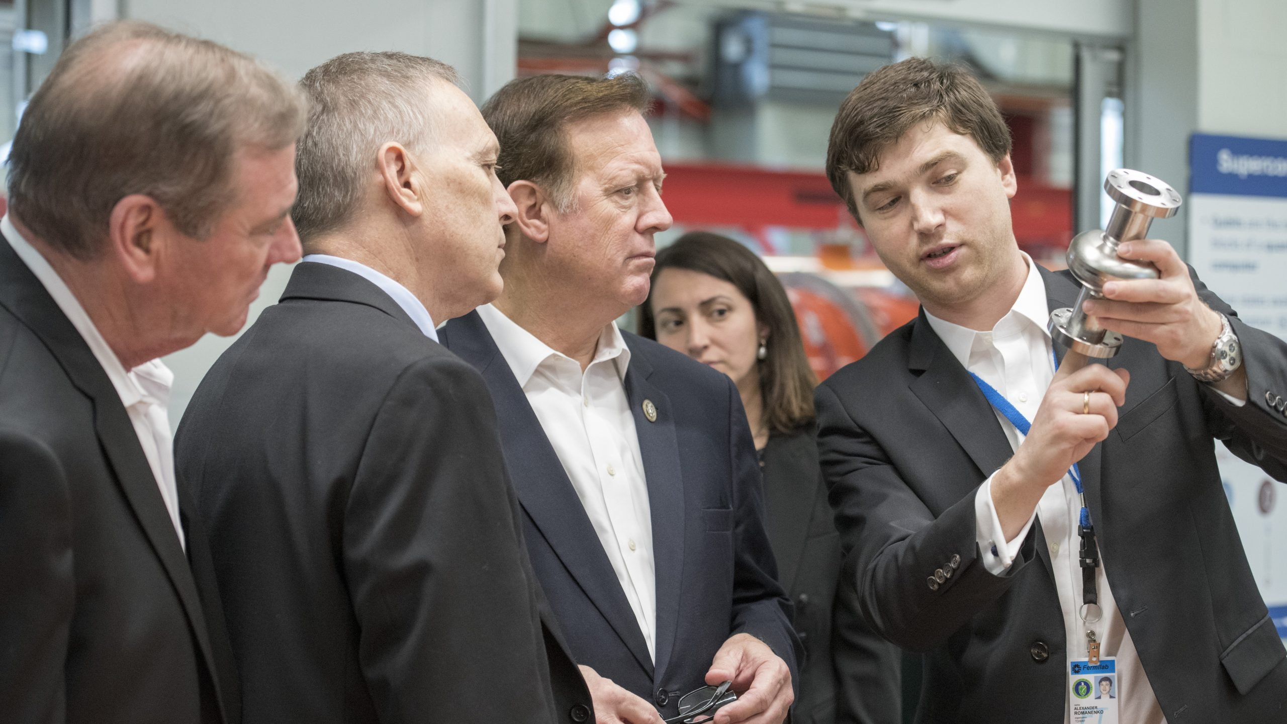 Congressmen (from left) Neal Dunn, Andy Biggs and Randy Weber listen to Alex Romanenko as he explains the potential applications of small, superconducting radio-frequency cavities in quantum computing. Photo: Reidar Hahn
