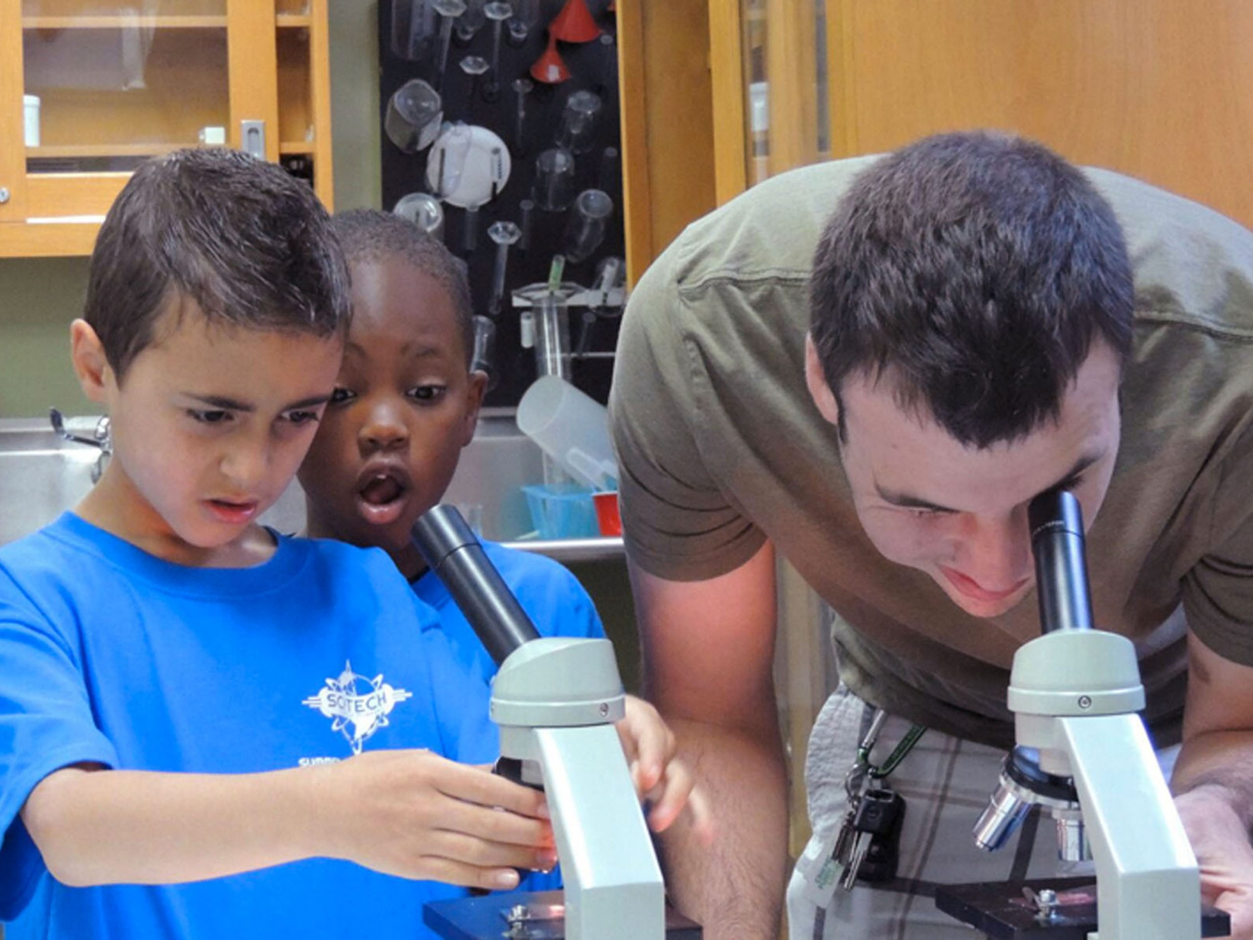 A volunteer helps two visitors use microscopes during science camp. Photo: SciTech Museum