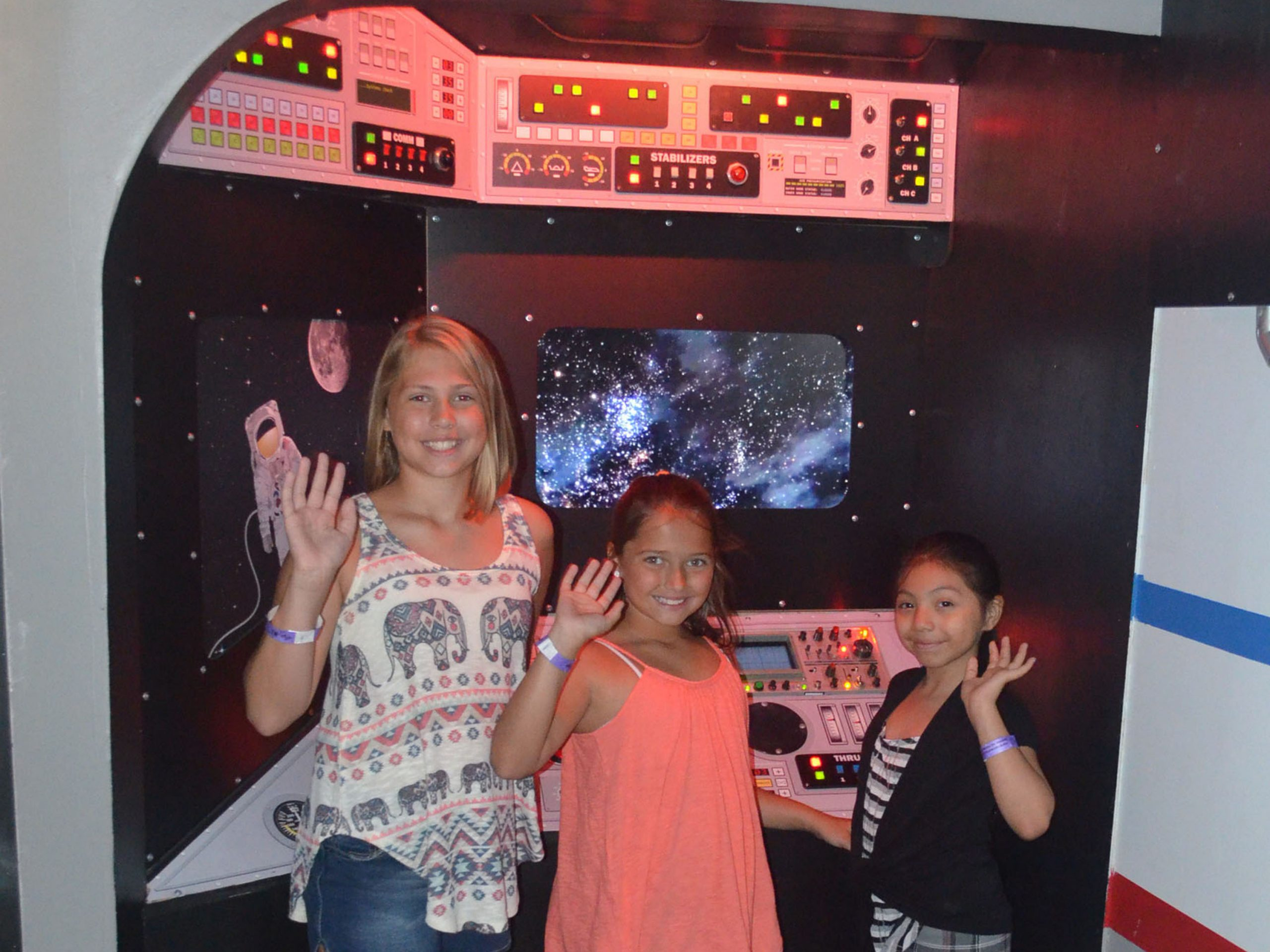 "Three visitors say hello in the control room of the exhibit ""Space Travels."" Photo: SciTech Museum"