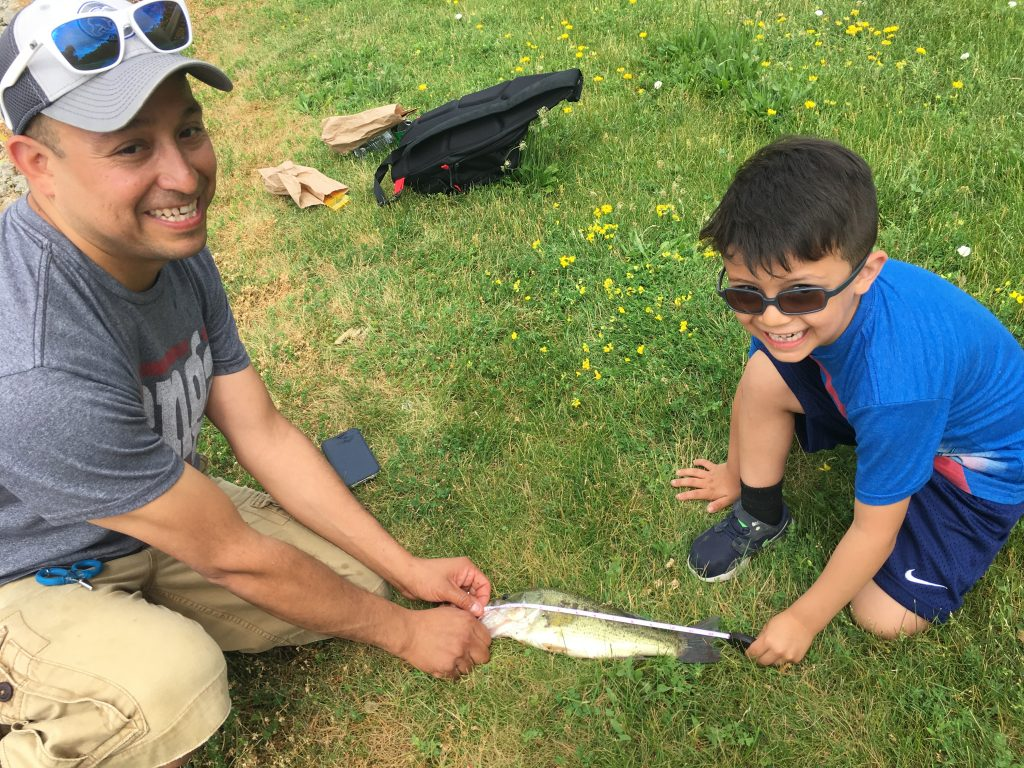 Luis Colmenares and his son Joaquin measure their 1st place winning bass
