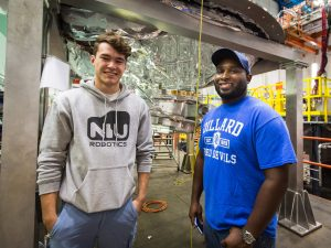 Josh Helsper, left, and Donovan Tooke pose in front of some cryogenics on the floor of the CDF assembly hall. Helsper is an intern with SIST this summer and attends NIU. Tooke is an alumnus of SIST and is currently a crew chief in the Accelerator Division. Photo: Elliott McCrory, people