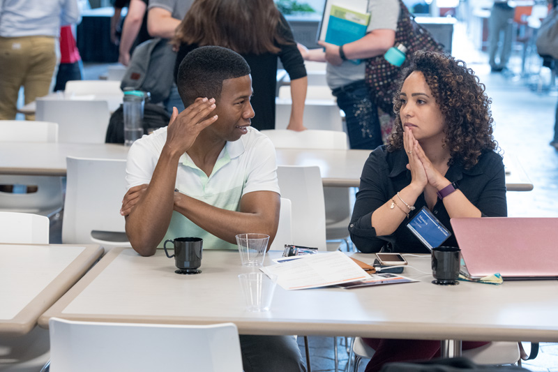 Fermilab Student and Postdoc Association officer Mônica Nunes, right, contemplates how smoothly the meeting is going with her friend. Photo: Reidar Hahn