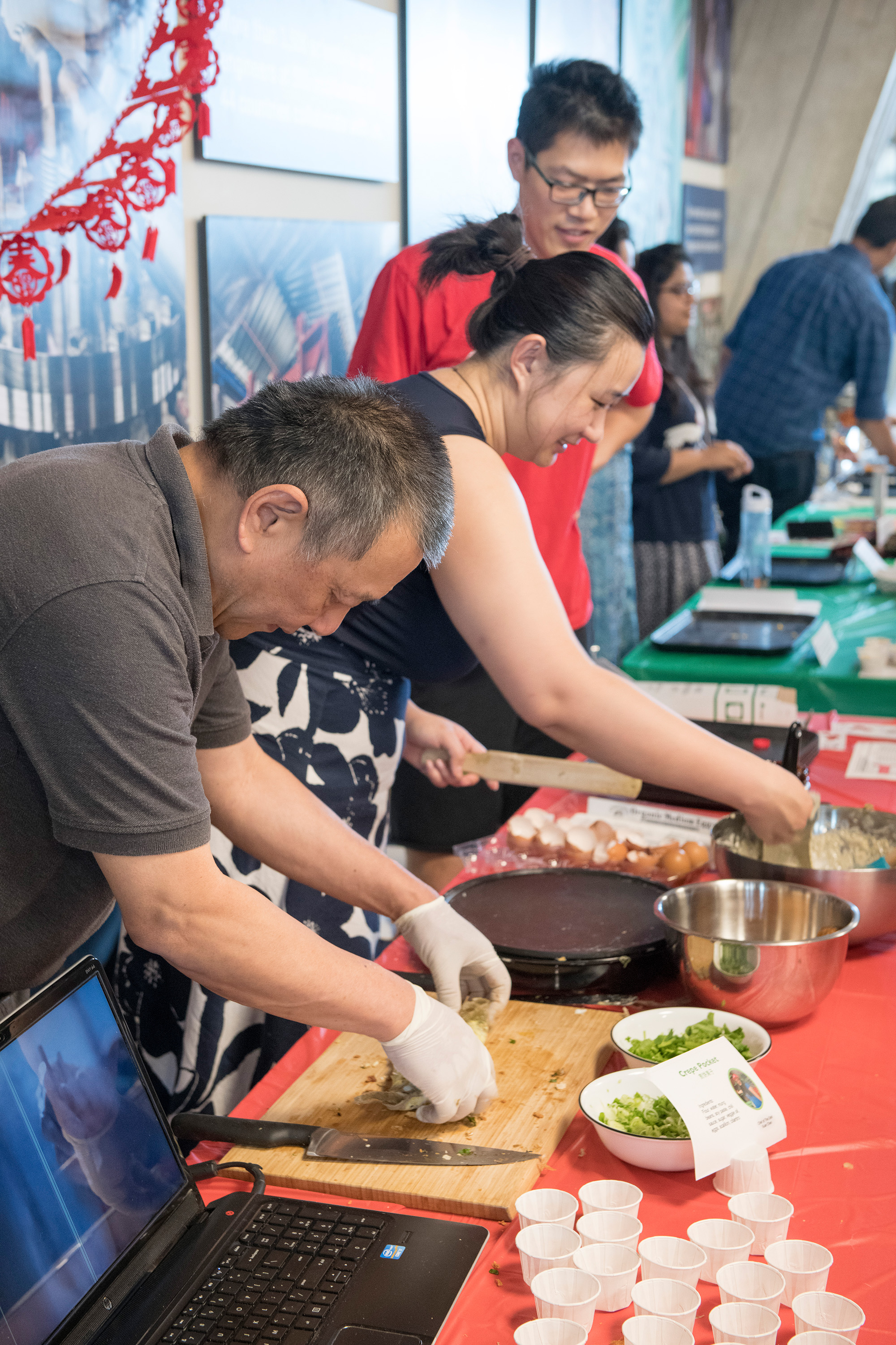 "Norman Ho and Xuan Chen, food ambassadors for China, prepare ""tastes"" for the International Taste of Fermilab. Photo: Reidar Hahn"