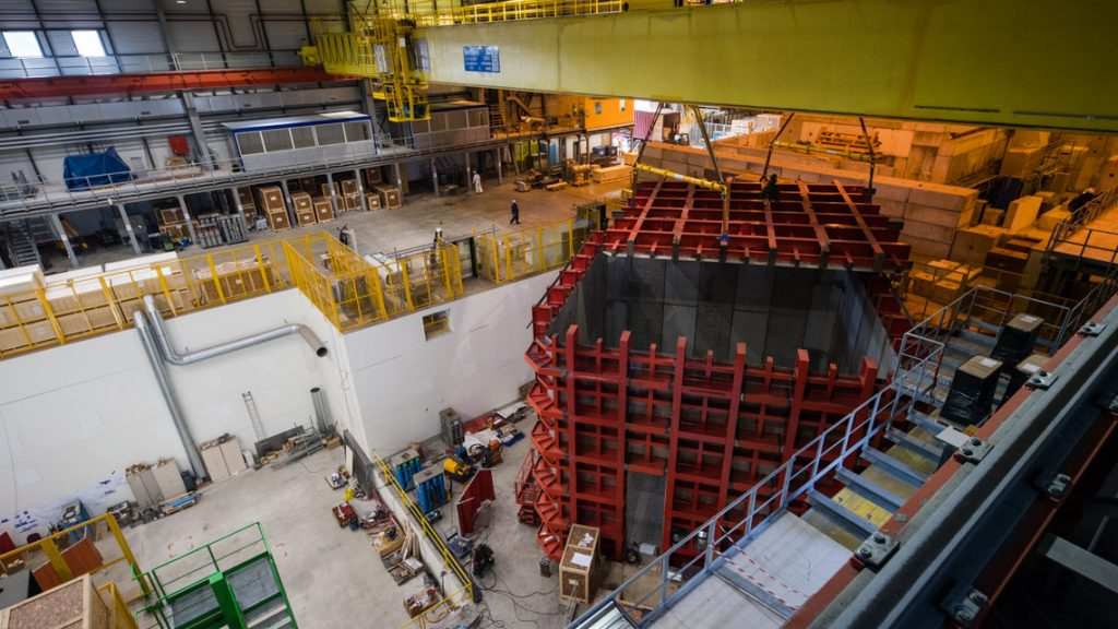 The steel cage for one of the two ProtoDUNE detectors is outfitted with a steel top, hoisted into position by a crane. Photo: CERN