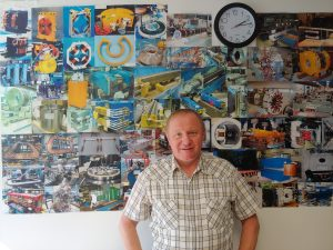 Sasha Makarov stands next to pictures of some of the magnets he has designed.