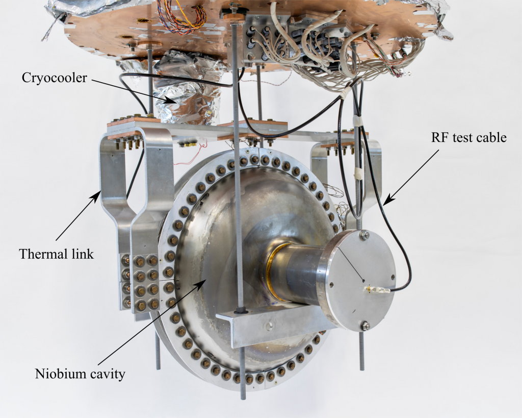 A superconducting radio-frequency accelerator cavity is mounted and connected to a cryocooler, cooling the cavity without the use of liquid helium. This new device could make it easier to produce high-average-power electron beams for industrial applications. Photo: Marty Murphy