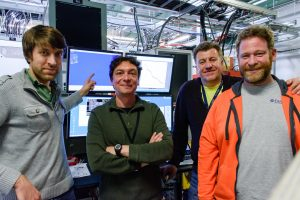 From left: Aleksandr Romanov, Giulio Stancari, Vladimir Shiltsev and Chip Edstrom, seen here in the Electrical Service Building, where some of the IOTA apparatuses and control reside, stand by screens that display IOTA activity. The photo was taken on Oct. 31, 10:15 p.m., when three electrons were circulating in the machine. Romanov points to the computer screen on the left, where a camera image of the beam was visible. The screen on the right shows one of the first plots of the discrete steps. Photo: Giulio Stancari