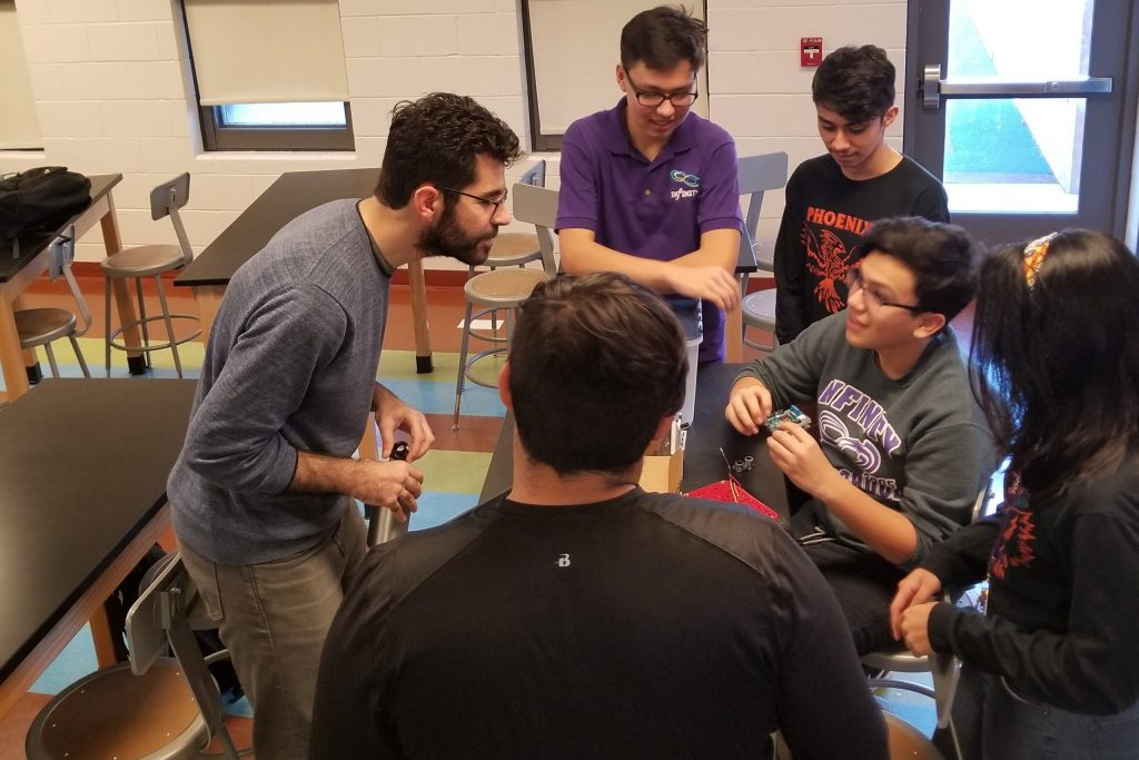 Manolis Kargiantoulakis works with students at Infinity Math Science and Technology High School on a coding exercise. Photo: Alexis Ross