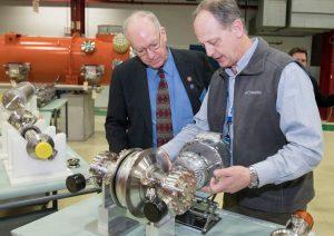 Fermilab engineer Chuck Grimm, right, shows Congressman Bill Foster an acceleration cavity coupler. Photo: Reidar Hahn