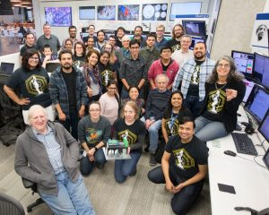 The MINERvA collaboration gathers to celebrate the end of data taking. MINERvA co-spokesperson Laura Fields, kneeling at center, holds a 3-D-printed model of the MINERvA neutrino detector. Photo: Reidar Hahn