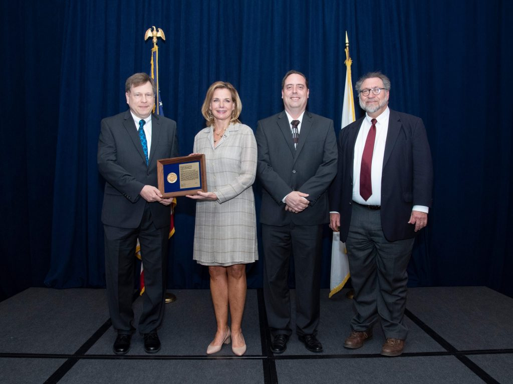 The Muon g-2 Project receives its DOE Achievement Award. From left: DOE Federal Project Director Paul Philp. National Nuclear Security Administration Undersecretary for Nuclear Security and Administrator Lisa Gordon‐Hagerty, Fermilab Muon g-2 Project Manager Chris Polly, DOE Federal Program Manager Ted Lavine. Photo: DOE