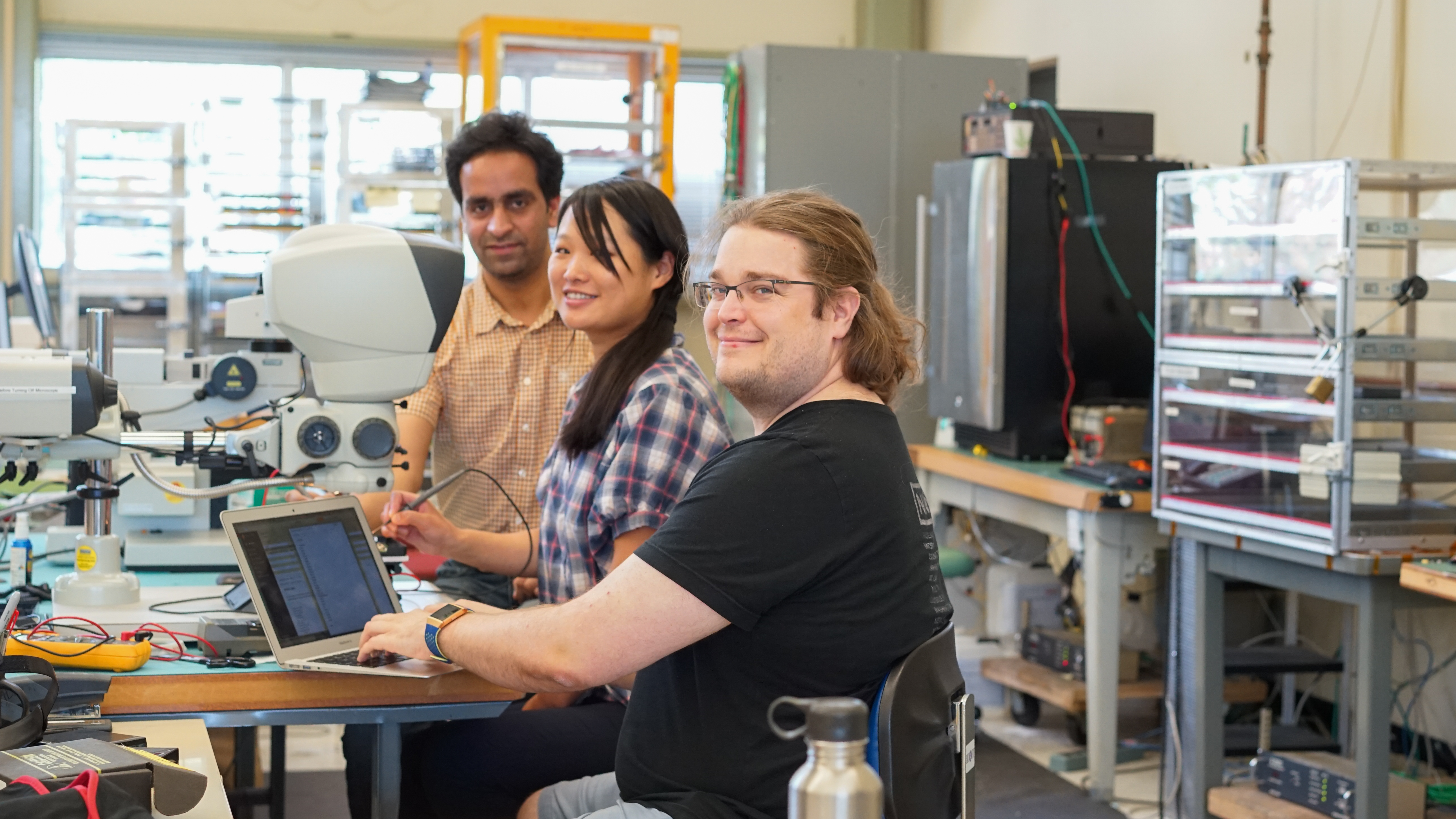 (1/2) Lindsey Grey, right, is an associate scientist in the Scientific Computing Division working on early prototypes of readout boards for the MIP timing detector endcap timing layer. This group is determining by hand the functioning yield of bump bonds that attach a low-gain avalanche detector (a silicon sensor that can be used as a precision timing device) to a simple interposer PCB to make a prototype sensor assembly. From left: Aashaq Shah (Delhi University), Miaoyuan Liu (Fermilab), Lindsey Gray (Fermilab). detector technology, people Photo: Leticia Shaddix