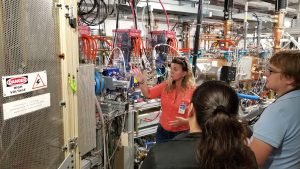 (2/4) Fermilab scientist Fernanda Garcia explains to interns Amanda Babcock, DOE Office of Science, and Bailey Bedford how the PIP-II ion source will provide particles for Fermilab's new accelerator using an electric field of 30,000 volts. people, PIP-II Photo: Kurt Riesselmann