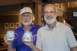 Fermilab retirees and golfers Tony Leveling (left) and Bob Hively hoist their commemorative cups for winning the Wednesday Bliss Creek golf league playoff match on Aug. 28. people Photo: Elliott McCrory