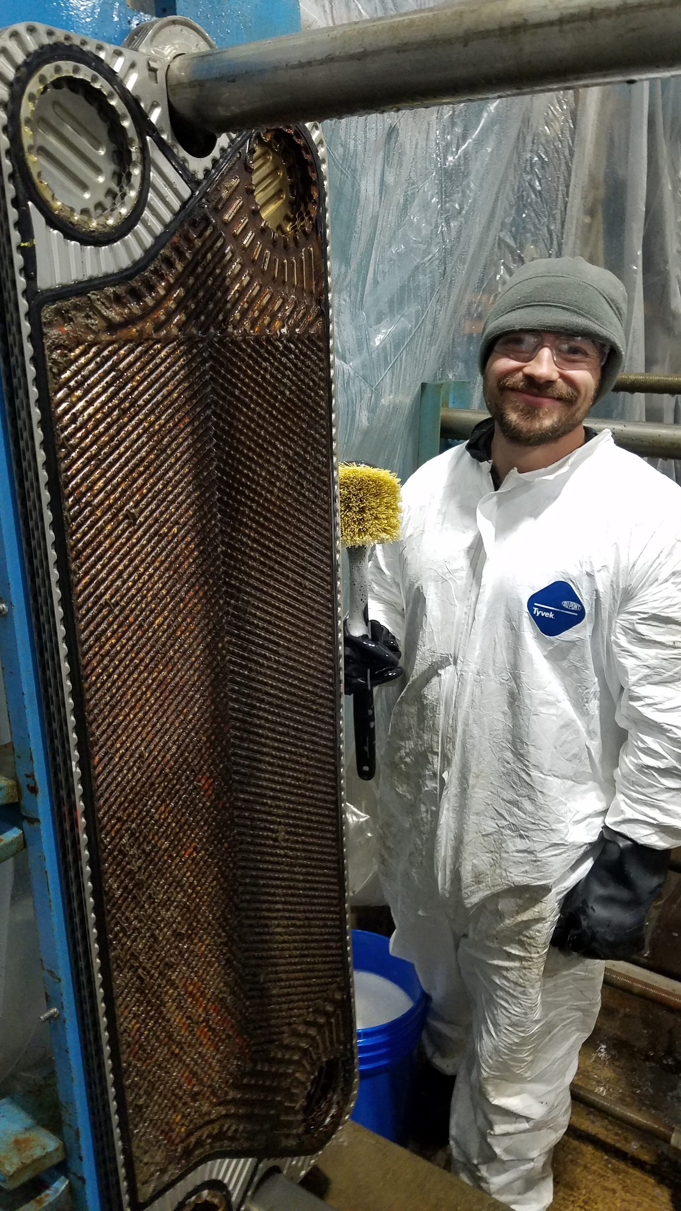 Ernest Feret smiles for the camera during an IB-1A heat exchanger cleaning. Each heat exchanger has 237 plates that need to be pressure-washed and scrubbed front and back. This is part of our yearly maintenance. people Photo: Randy Ward