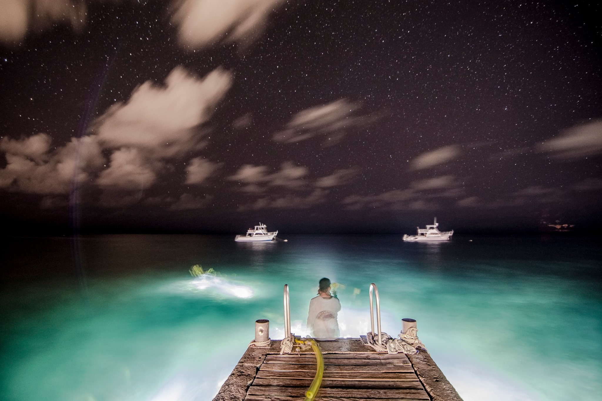 Fermilab Dive Club members enjoy a night snorkel in the Grand Cayman while the camera looks on. people Photo: Derek Plant