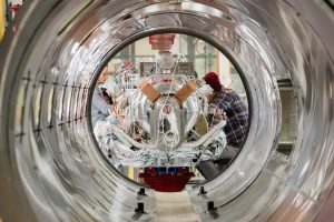(3/4) From left: Technicians Alexander Hogberg, Mayett Verano (faintly visible) and Shawn Murray work on the SSR1 cavity string about to be inserted into the outer vacuum vessel (seen in the foreground). accelerator, accelrator technology, people, cryomodule, PIP-II Photo: Tom Nicol