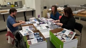 Scientists Luke Pickering, Kirsty Duffy and Anne Norrick met for a work party on Feb. 27. With music playing in the background, they prepared handouts for an outreach event in March. people, lab life Photo: Kurt Riesselmann
