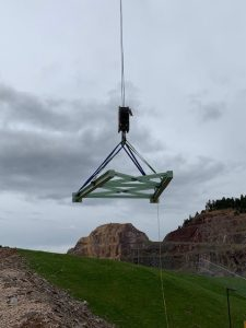 At Sanford Lab, a piece of the discharge truss for the conveyor system that will transport excavated rock to its final location is hoisted into place at the open cut in Lead, South Dakota. LBNF, Long-Baseline Neutrino Facility, neutrino, construction Photo: Jeffrey Shearer