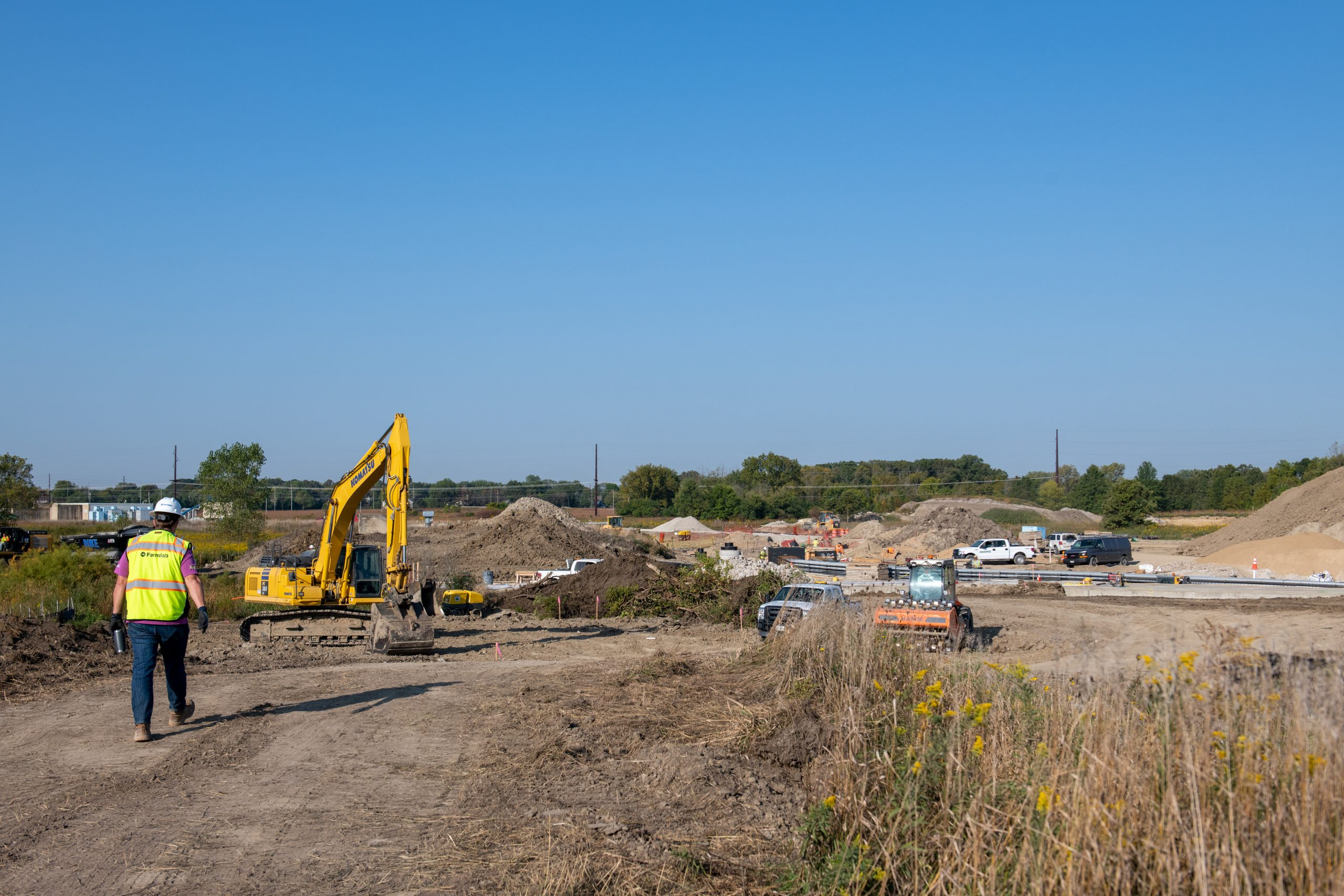 Excavators move earth to prepare the Fermilab site for new accelerator and beam infrastructure, part of the future Long-Baseline Neutrino Facility.