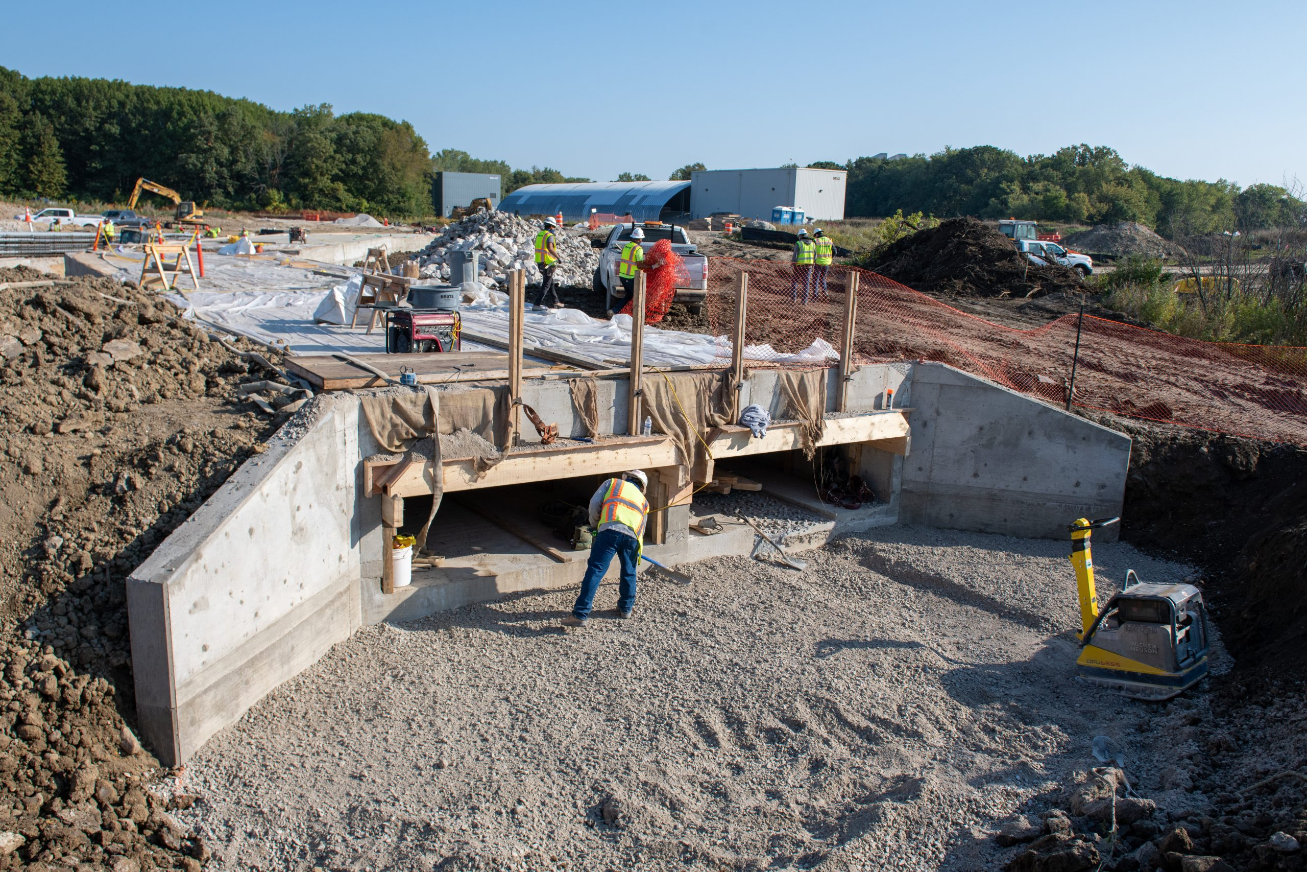 Crews build a new roughly 500-foot-long box culvert for the new alignment of Indian Creek, a small stream on the Fermilab site, which will flow under one of the site's main roads. The culvert includes a naturalized channel for fish.