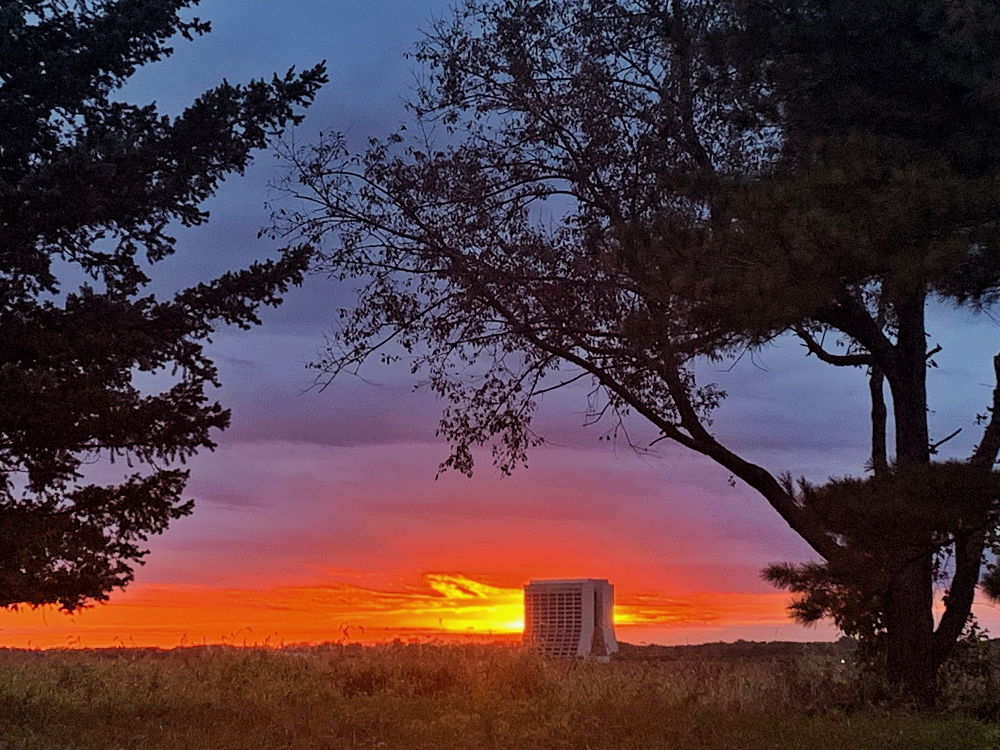 The sun peeps through the clouds, pouring molten gold on the sky, just before setting behind Wilson Hall on a cloudy Sept. 29. In this moment, one can imagine the fabled rising phoenix. nature, landscape, sky, sun, sunset, cloud, building, Wison Hall Photo: Sudeshna Ganguly