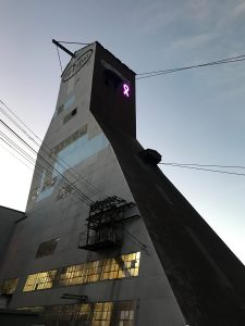 The Ross Headframe, located at Sanford Underground Research Facility in Lead, South Dakota, is adorned with a pink ribbon in support of Breast Cancer Awareness. LBNF, Long-Baseline Neutrino Facility Photo: David A. Smith