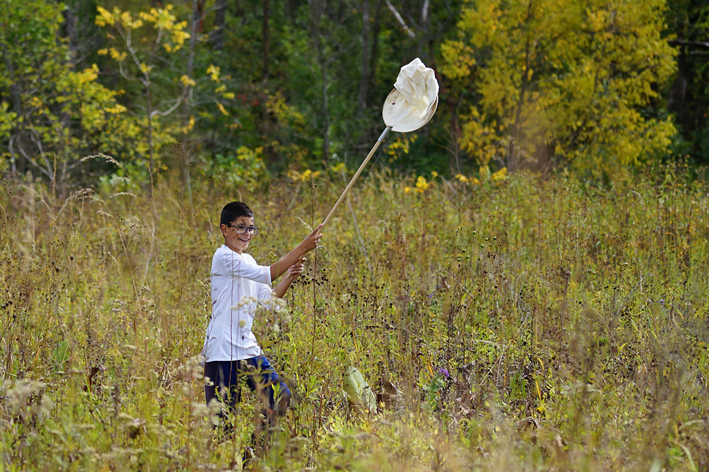 One student happily chases insects. STEM, education, outreach, people, ecology, prairie Photo: Leticia Shaddix