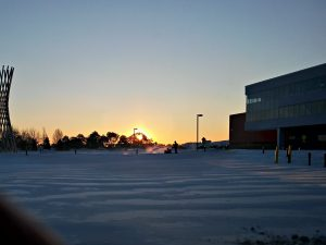 The sun rises over campus as snow is plowed in January. sun, sky, campus, snow, people Photo: Krzysztof Kompiel