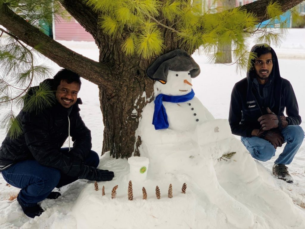 Creators Vibodha Mudiyanselage and N.C. Perera pose with Mr. Misty Having a Starbucks While Working on His Project With His Mac Under a Tree, which won favorite snowman in the competition. people, snow, winter, event, tree