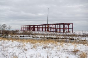 Fermilab is starting to stand up the structural steel for the PIP-II Cryogenic Plant Building. This shows the building from the perspective of the AZero service building along Main Ring Road. building, PIP-II, construction, winter Photo: Ryan Postel