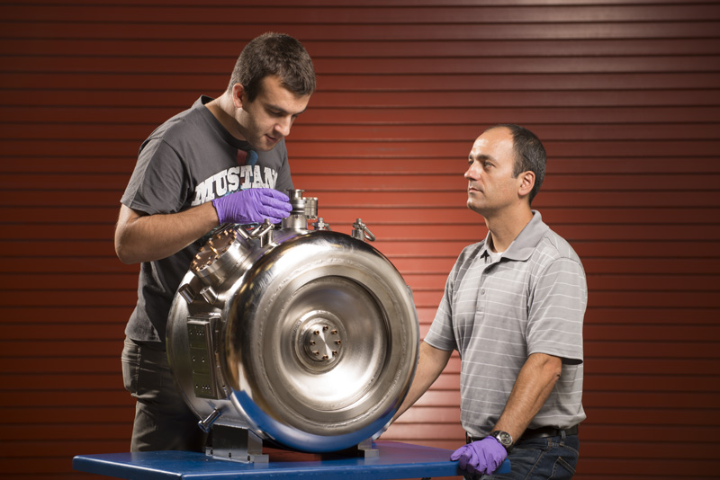 Operating at 325 MHz, the single-spoke resonators, or SSRs, are key to the PIP-II cold linac's performance. The PIP-II SSR technical team declared 3.25 to be Spoke Day. Fermilab engineers Donato Passarelli and Leonardo Ristori pose with one here. people, PIP-II, accelerator technology, cavity Photo: Reidar Hahn, Fermilab
