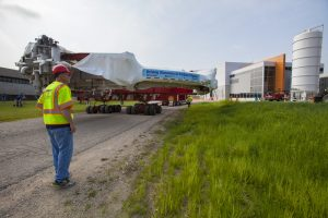 On July 26, 2014, the Muon g-2 magnet ring traveled to its new home on the Fermilab site, the brand-new MC-1 building. Scientists will announce the first results from the Muon g-2 experiments at 10 a.m. CDT on April 7, 2021. Muon g-2, magnet, campus, building, people Photo: Cindy Arnold, Fermilab