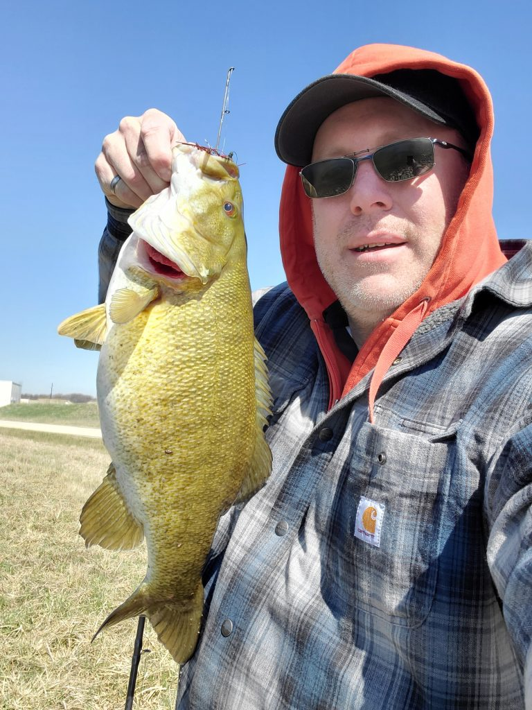 On April 2, 2021, Fermilab employee Kelly Sedgwick poses with a smallmouth bass (5.42 pounds, 20.75 inches, for the record) that he caught in one of the Main Injector ponds. campus, people, nature, fish, bass Photo: Kelly Sedgwick