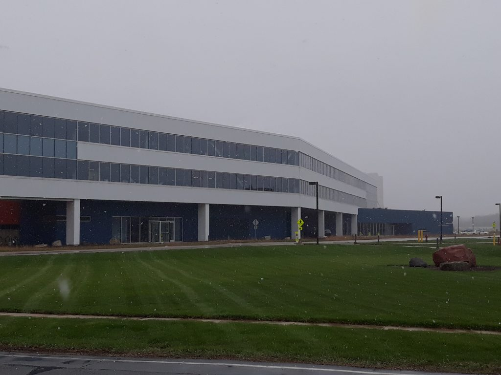 In late April 2021, the grass is bright green and snow falls from a gray sky in front of the IARC building. snow, spring, IARC, campus Photo: Luciano Elementi