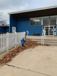 A child wearing a gray toboggan and blue coat faces away from the camera, trudging in furry boots through a line of leaf-blown brown leaves on a large sidewalk against a white picket fence and into a bright blue building, set against a gray sky.