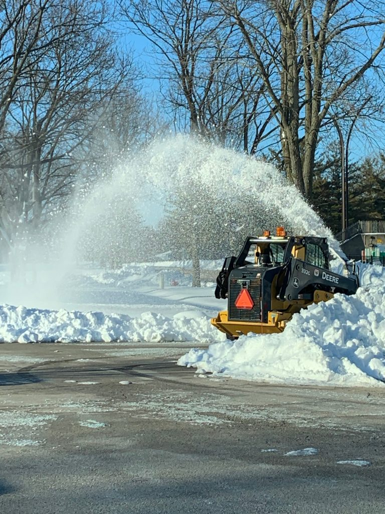 A small yellow John Deere tractor pushes through a large pile of snow. A tall spray of snow being removed shoots over the tractor. Clean pavement is in the foreground. Bare trees and blue skies are in the background.