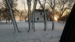 Sun sets behind a white two-story house and trees with snow on them vertically are in foreground.