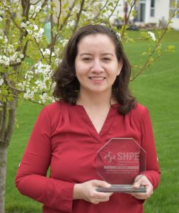Jeny Teheran holds her SHPE award, which is made of transparent glass with words etched on it. She wears a red shirt and the background is a bright green field and blossoming tree or shrub.