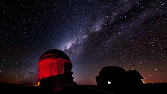 A starry night sky with purple diagonal stripe from lower left to upper right corner above an observatory lit up in bright red. A shadow of a building or facility is in the lower right corner.