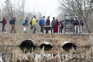Students and teachers bundled in jackets and scarves stand in a sort-of line with a cart hauling an experiment on a dreary Fermilab campus. The sky is gray, there is dead straw in the foreground and a small waterway.