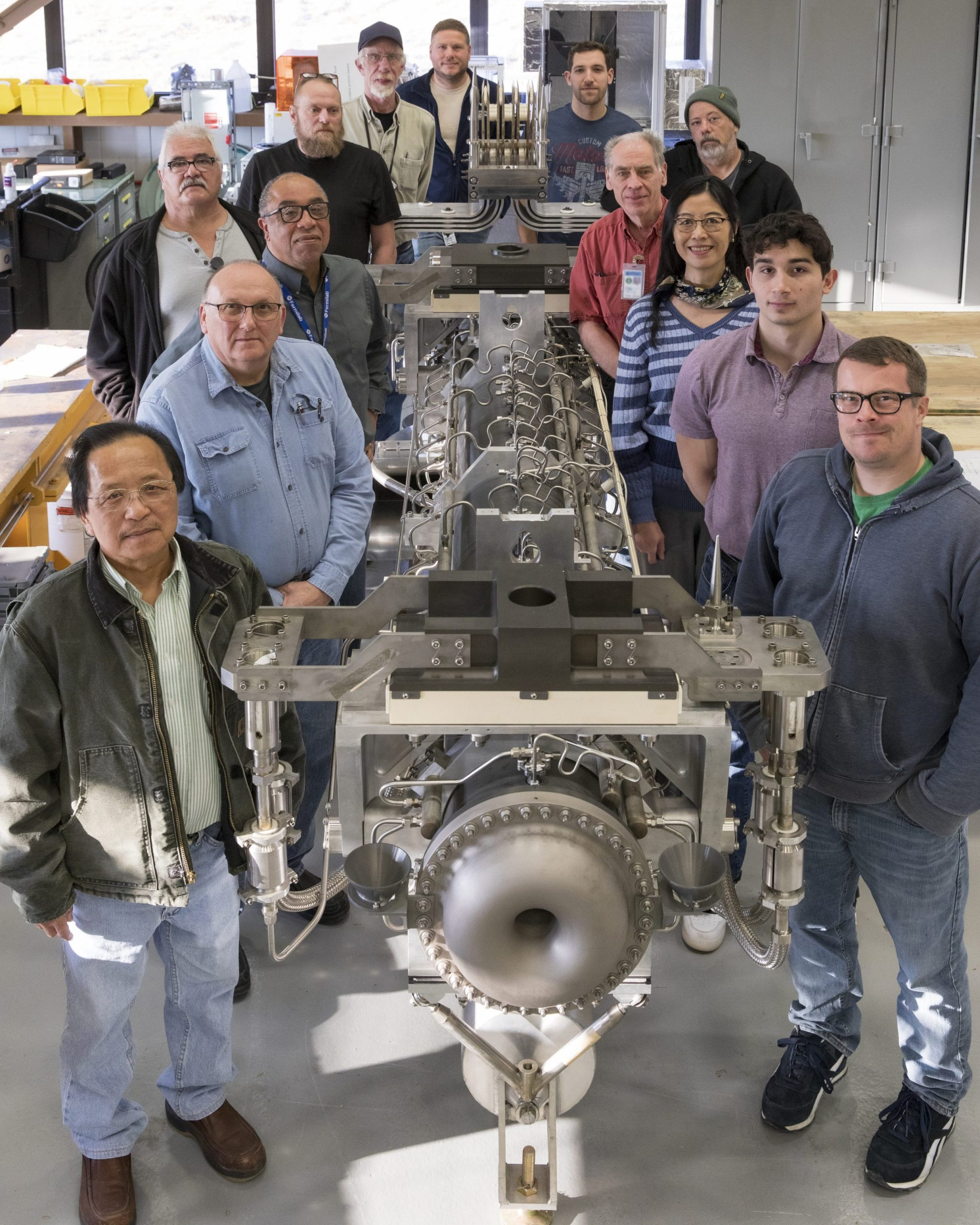 Twelve men and one woman in casual dress gather around a large pewter-colored piece of equipment.