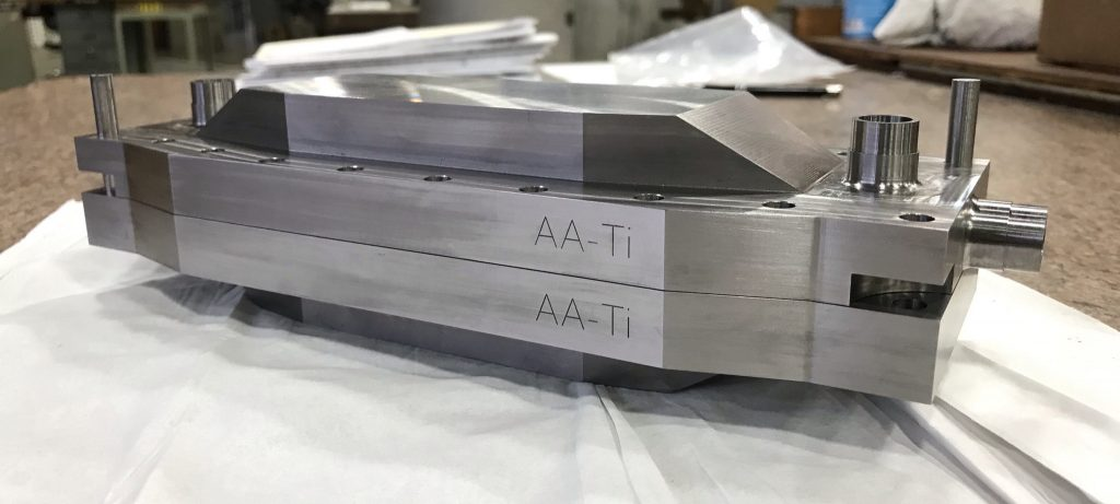 A silver object that is shaped somewhat like a toy battleship, with AA-Ti engraved twice on the side facing the camera, sits on a white sheet on a table. In the background, a workshop and Windex.
