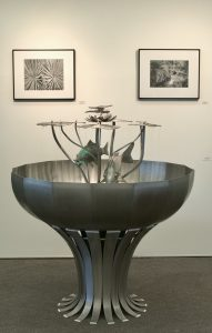 Photo of metal sculpture (described in caption) sitting on the floor in front of two black-and-white photos of plants hung on a gallery wall.