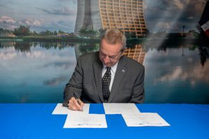 A man in a charcoal suit and tie sits at a table with a blue tablecloth, signing documents with a pen. Behind him, a large print of Wilson Hall, a concrete brutalist building, and a reflection pool on a cloudy yet blue sky day with rays of sun beaming down.