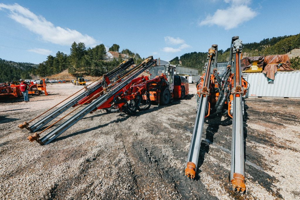 An orange and silver drill rig (a tractor-like apparatus with two parallel arms that reach above the cab and then make a steep diagonal to the ground) and several red and silver drill rigs sit in the foreground of a silty construction site. Other equipment is in the midground and hills filled with evergreens and blue sky above in the background.