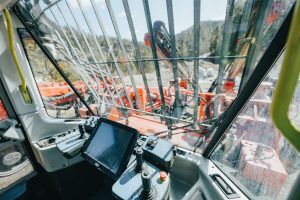 Inside a window, a tablet and dashboard. The window itself appears to have many vertical bars and two or three horizontal bars overlooking a construction site with an orange truck of some sort, maybe a crane, hills in the background and blue sky.